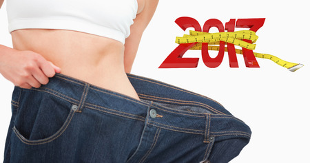 lost in space: Close up of a woman waist who lost a lot of weight against new year with tape measure