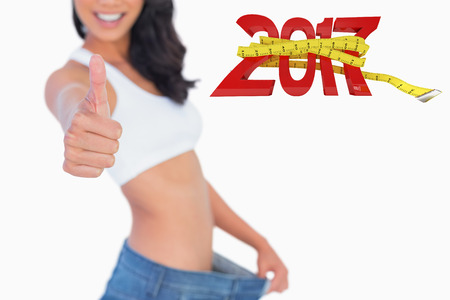 Victorious woman holding her too big pants thumbs up against digitally generated image of new year with tape measure