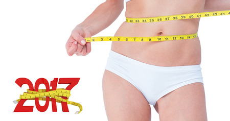 digitally generated image: Attractive woman measuring her belly against digitally generated image of new year with tape measure