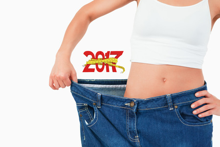 digitally generated image: Digitally generated image of new year with tape measure against midsection of woman wearing large jeans Stock Photo