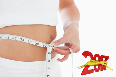 waist: Closeup midsection of woman measuring waist against digitally generated image of new year with tape measure