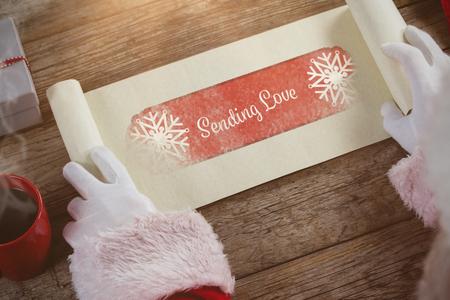 sending: Close-up of santa claus opening scroll against banner sending love