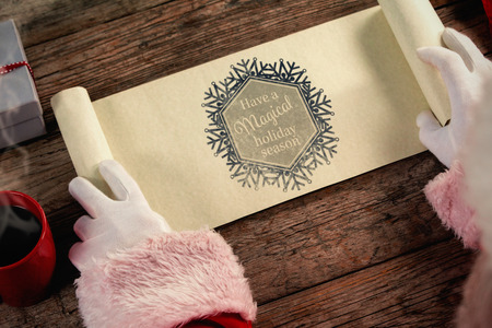santa suit: Close-up of santa claus opening scroll against snowflake have a magical holiday season Stock Photo