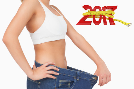 image size: Digitally generated image of new year with tape measure against midsection of slim young woman wearing big size jeans Stock Photo