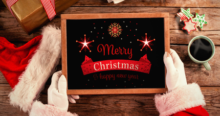 christmas gift box: Santa claus holding a slate with merry christmas text against christmas card