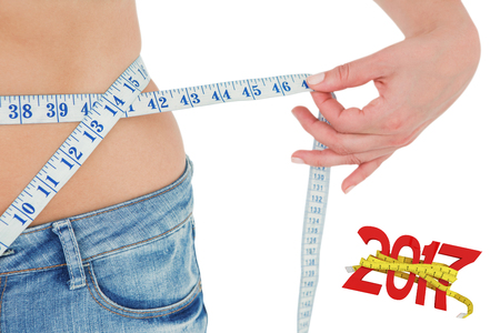 digitally generated image: Woman measuring her waist  against digitally generated image of new year with tape measure Stock Photo