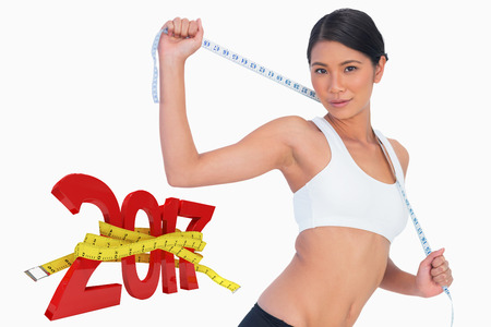 Slim woman holding her measuring tape against digitally generated image of new year with tape measure
