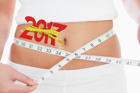 measuring waist: Closeup midsection of woman measuring waist against digitally generated image of new year with tape measure