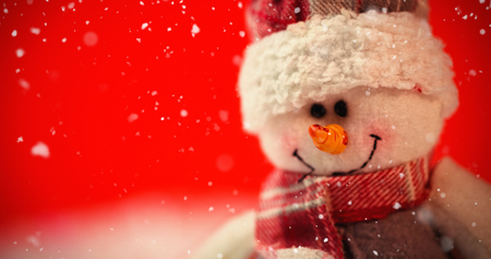 Snow falling against close-up of snowman