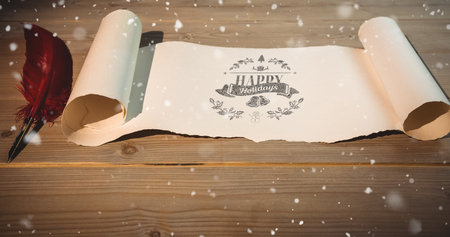 Christmas greeting  against high angle view of old blank scroll paper and quill Stock Photo