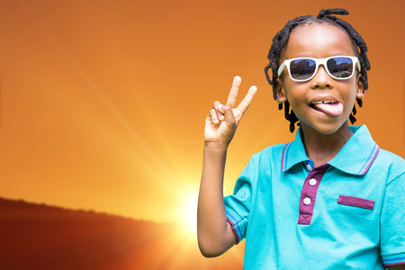 Child making wince against scenic view of landscape against orange sky Stock Photo