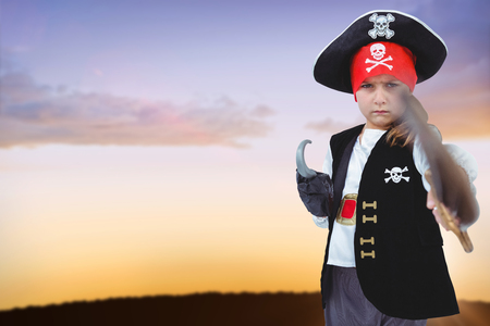 Masked girl pretending to be pirate against silhouette landscape against sky Stock Photo