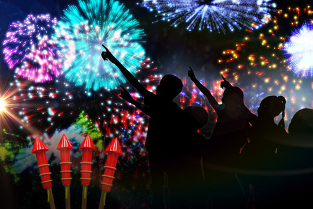 artifice: Silhouette children pointing against colourful fireworks exploding on black background
