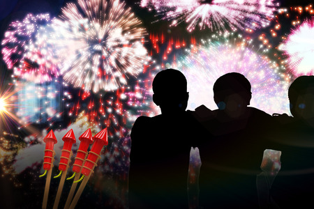 artifice: Silhouette children standing against colourful fireworks exploding on black background