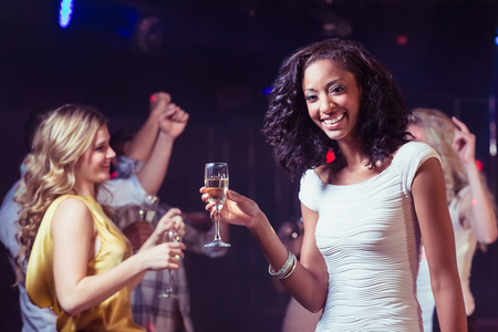 dancing club: Portrait of woman holding champagne flute while dancing in club
