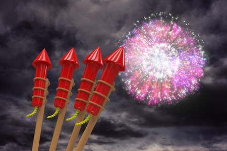 Rockets for fireworks against colourful fireworks exploding on black background Stock Photo