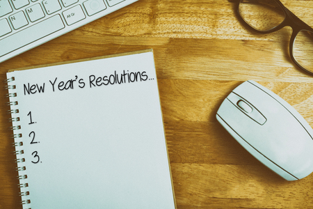 new years resolution: New years resolution list against overhead of notebook and glasses