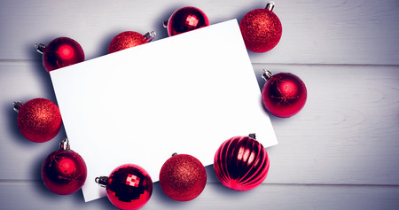 against white: Red christmas baubles surrounding white page against white wooden background Stock Photo