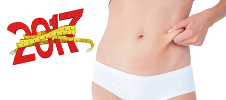 Woman posing without any fat on her belly against digitally generated image of new year with tape measure