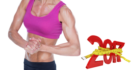 Female bodybuilder flexing in sports bra and shorts against digital image of new year with tape measure Stock Photo