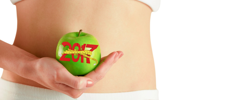 slim women: Slim woman holding green apple against digitally generated image of new year with tape measure