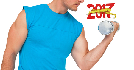 Close-up mid section of fit man exercising with dumbbell against digital image of new year with tape measure