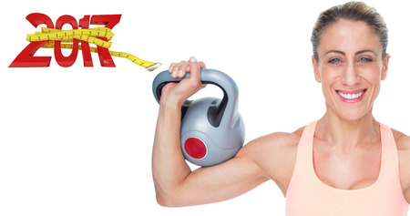 Happy female crossfitter lifting kettlebells looking at camera against digital image of new year with tape measure