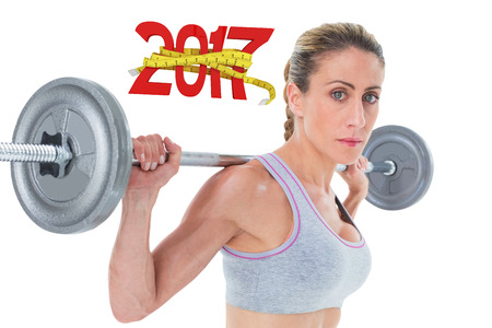 lean out: Strong female crossfitter lifting barbell behind head looking at camera against digitally generated image of new year with tape measure