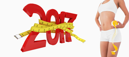 buttocks: Female slender body in sport underwear holding orange against digitally generated image of new year with tape measure