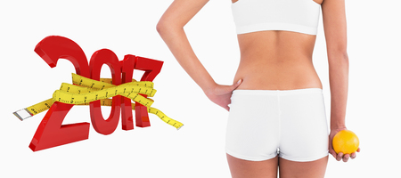 Rear view of female slender body in shorts against digitally generated image of new year with tape measure