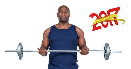 Fit man lifting heavy barbell against digital image of new year with tape measure