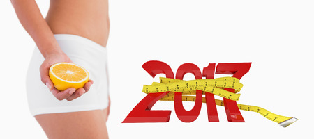 digitally generated image: Slender female body holding half orange against digitally generated image of new year with tape measure