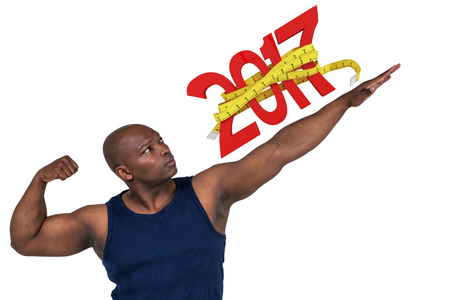 Fit man posing to camera  against digitally generated image of new year with tape measure