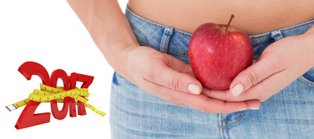 Fit woman standing with red apple against digitally generated image of new year with tape measure