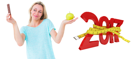 Smiling blonde holding bar of chocolate and apple against digitally generated image of new year with tape measure