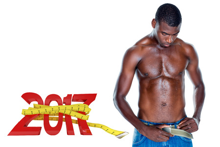 undressing: Fit shirtless young man against digitally generated image of new year with tape measure