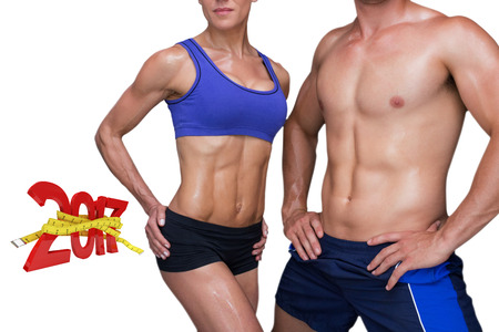 mid adult men: Bodybuilding couple against digitally generated image of new year with tape measure