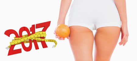 digitally generated image: Midsection of woman holding orange against digitally generated image of new year with tape measure Stock Photo