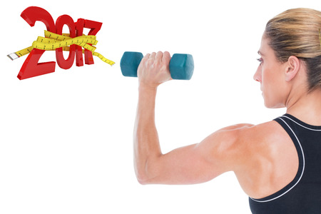 digitally generated image: Female bodybuilder holding a blue dumbbell against digitally generated image of new year with tape measure