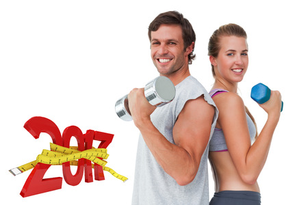 Portrait of a fit couple exercising with dumbbell against digitally generated image of new year with tape measure