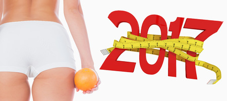 midsection: Midsection of fit woman with orange against digitally generated image of new year with tape measure
