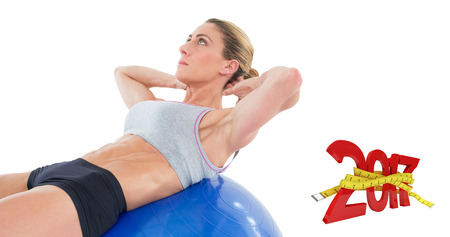 sit ups: Fit woman doing sit ups on blue exercise ball against digital image of new year with tape measure