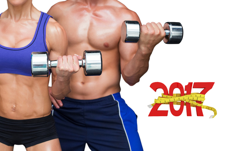 Bodybuilding couple against digitally generated image of new year with tape measure