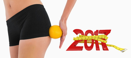 buttocks: Female buttocks with orange rolling on it against digitally generated image of new year with tape measure