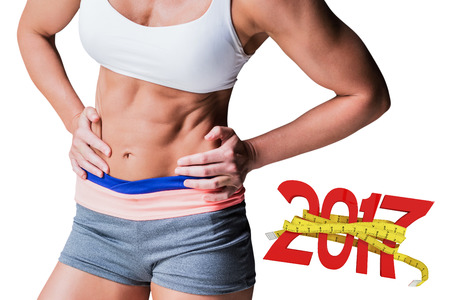 midsection: Midsection of muscular female athlete against digitally generated image of new year with tape measure Stock Photo