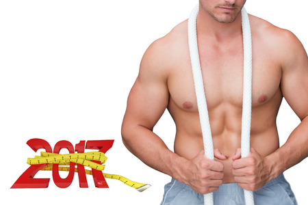 Handsome bodybuilder against digitally generated image of new year with tape measure Stock Photo