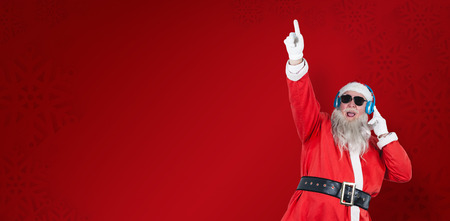 Santa Claus playing DJ with raised hand against red snowflake background 版權商用圖片