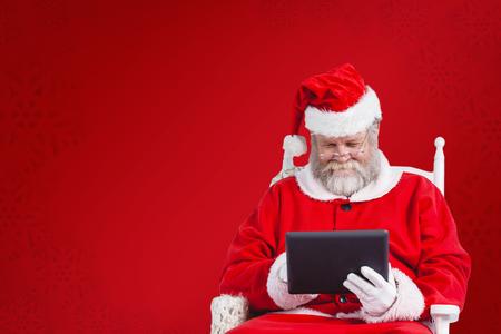 Santa Claus che esamina compressa digitale contro il fondo rosso del fiocco di neve Archivio Fotografico - 66395919