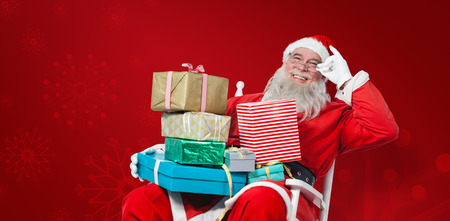 chritmas: Cheerful Santa Claus holding Chritmas presents while sitting on chair against red snowflake background