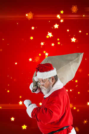 Santa Claus looking at wristwatch while holding sack full of Christmas gifts against bright star pattern on red Stock Photo